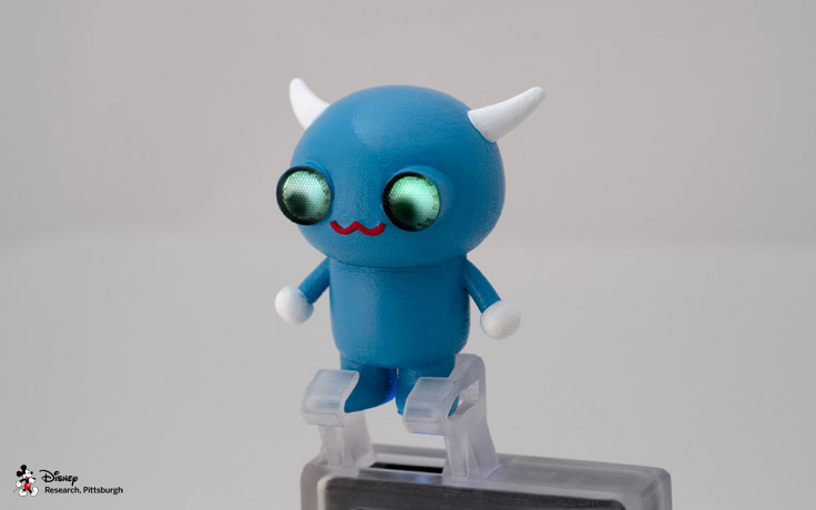 A 3D printed mobile projector accessory with embedded light pipes to map a projected image onto a character's eyes. The character's eyes respond to user interaction such as sound or physical movement.